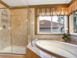 bathroom with framed glass shower, mirror and window